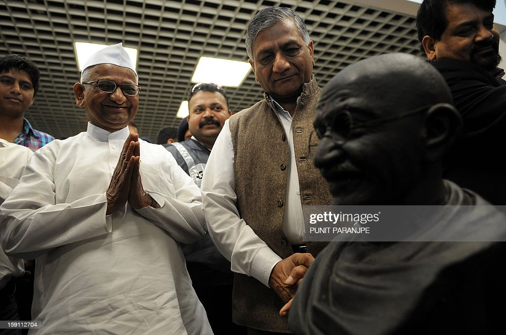 Indian anti-corruption activist Anna Hazare (2L) and retired Indian Army General V.K.Singh (2R) pay their respects to a statue of Mahatma Gandhi during a news conference at the international airport terminal in Mumbai on January 8, 2013. Gandhi's pair of iconic spectacles, a famous wooden 'charkha' which he personally used, a signed prayer book, several letters and other documents pertaining to Gandhi's life, and 24 other personal memorabilia were auctioned in London on April 17, 2012 and purchased by Indian industrialist Kamal Morarka who handed over the memorabilia to Hazare and his team. The memorabilia will be showcased in a tour around the country.
