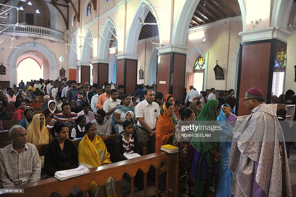 Indian Arch Bishop of Hyderabad, Thumma Bala (R), marks the symbol of the cross with ash on the forehead of a Christian devotee during an Ash Wednesday service at Saint Mary's Basilica in Secunderabad, the twin city of Hyderabad, on February 13, 2013. Catholics began the 40 day Lenten season, by observing observe Ash Wednesday, which culminates in Holy Week. AFP PHOTO / Noah SEELAM