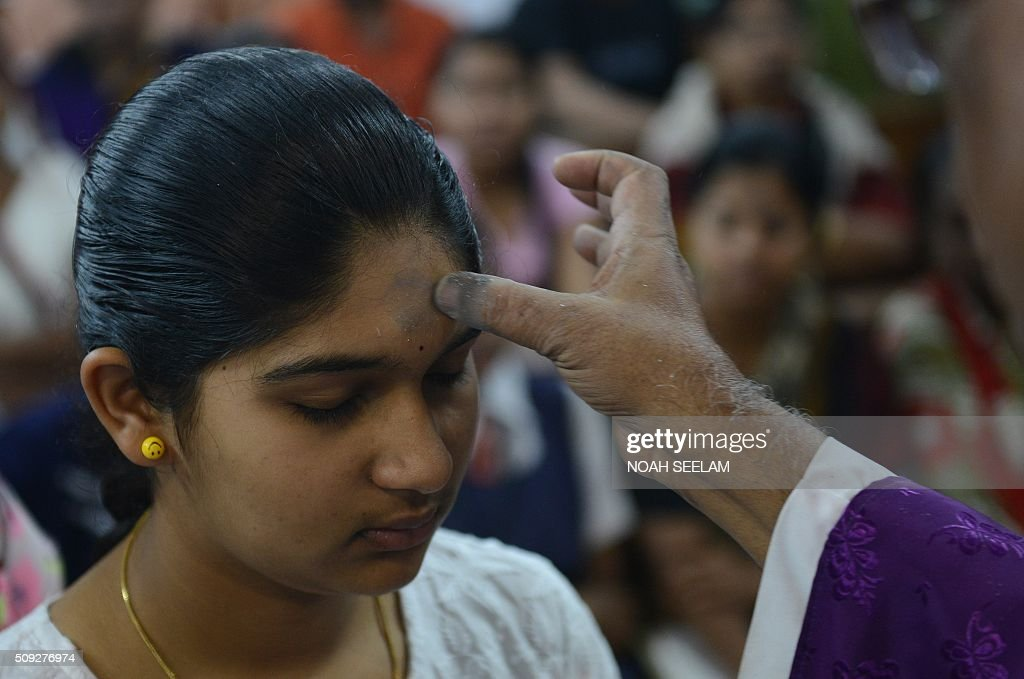 Indian Arch Bishop of Hyderabad, Thumma Bala (R) marks the symbol of the cross with ash on the forehead of a young Christian devotee during an Ash Wednesday service at Saint Mary's Basilica in Secunderabad, the twin city of Hyderabad, on February 10, 2016. Catholics began the 40 day Lenten season, by observing Ash Wednesday, which culminates in the Holy Week. AFP PHOTO / Noah SEELAM / AFP / NOAH SEELAM