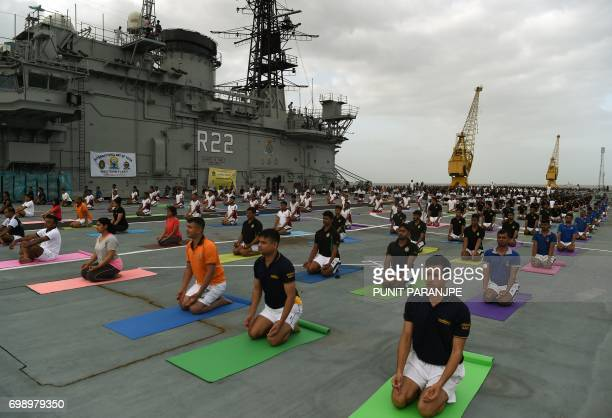 Indian Armed Forces personnel take part in a yoga sesssion to mark International Yoga Day on the Indian Navy aircraft carrier INS Viraat anchored at...