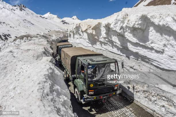 Indian army convoy passes through the snowcleared SrinagarLeh highway on May 12 2017 in Zojila 108 km east of Srinagar the summer capital of Indian...