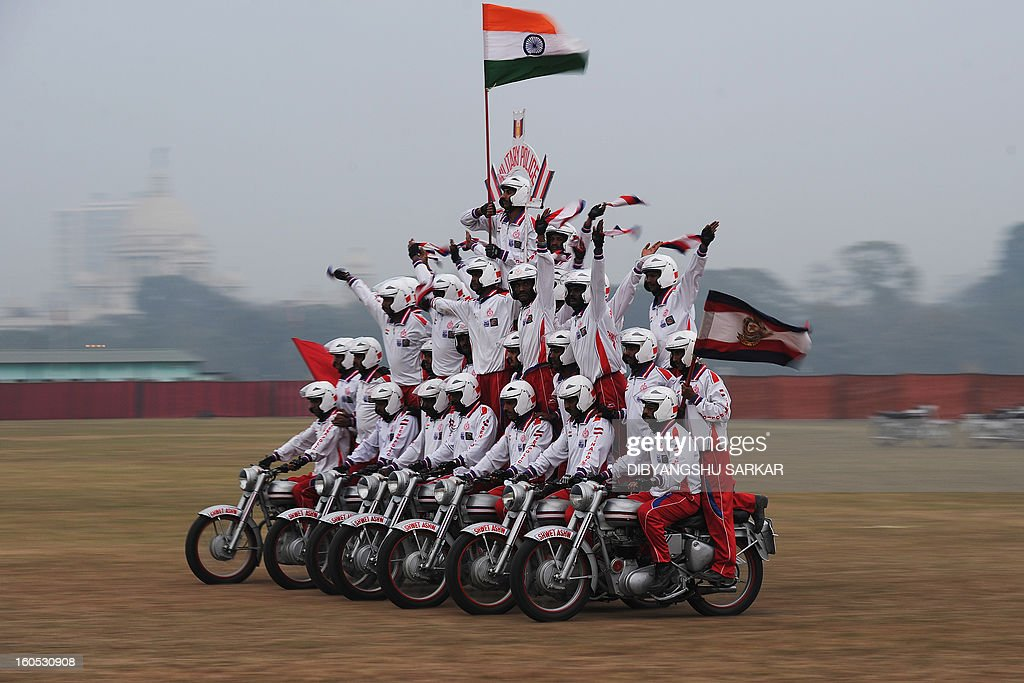 Indian Army daredevil motorcyle team members displays their skills during an Army weaponry exhibition in Kolkata on February 2, 2013. The event was held as a recruitment tool for young Indians to join the country's armed forces. AFP PHOTO/Dibyangshu SARKAR
