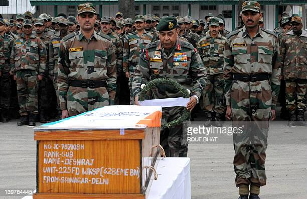 Indian Army Lieutenant General Syed Ata Hasnain prepares to lay a wreath onto a coffin during a funeral ceremony at a military garrison in Srinagar...