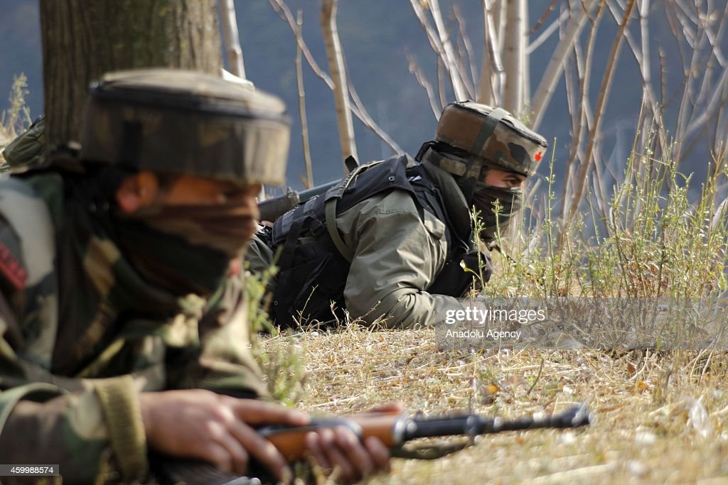 Indian army men stand on top of a mountain during an encounter between suspected militants and Army soldiers on their base at Mohra in Kashmir India...
