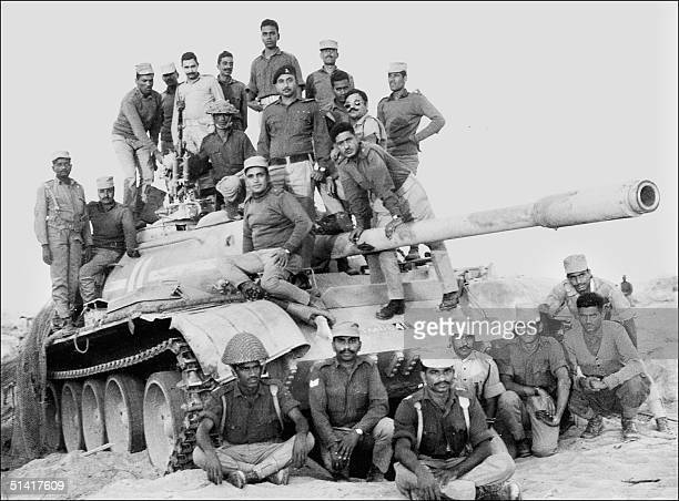 Indian army officers and soldiers stand 11 December 1971 atop a captured Pakistani tank in the desert of the state of Rajasthan during the...