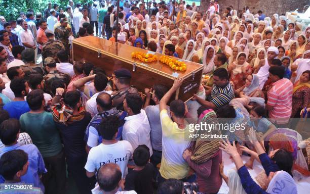 Indian Army personnel and family members carry the coffin of slain Indian soldier Lance Naik Ranjeet Singh to his home in Burn village about 28km...