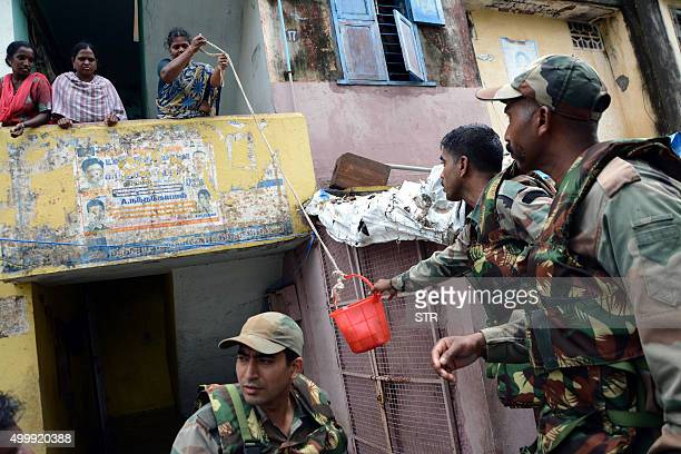 Indian army personnel deliver supplies to residents trapped by floodwaters in Chennai on December 4 2015 Thousands of rescuers are racing to evacuate...