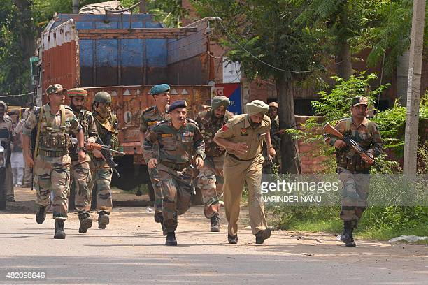 Indian Army personnel run during an encounter with armed attackers at the police station in Dinanagar town in the Gurdaspur district of Punjab state...