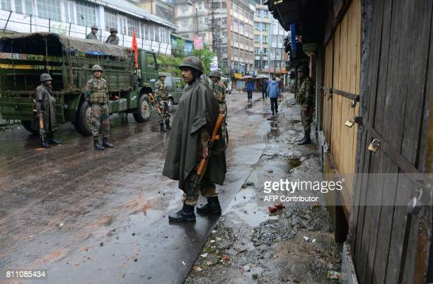 Indian army personnel stand guard along a street during an indefinte strike called by the Gorkha Janmukti Morcha in Darjeeling on July 9 2017 Fresh...