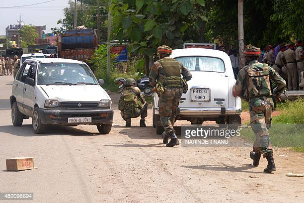 Indian Army personnel take position during an encounter with armed attackers at the police station in Dinanagar town in the Gurdaspur district of...