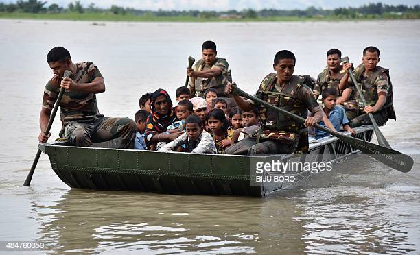 Indian army personnel transport villagers affected by flooding at Jaraguri village in Bongaigoan district some 160 km from Guwahati in the...