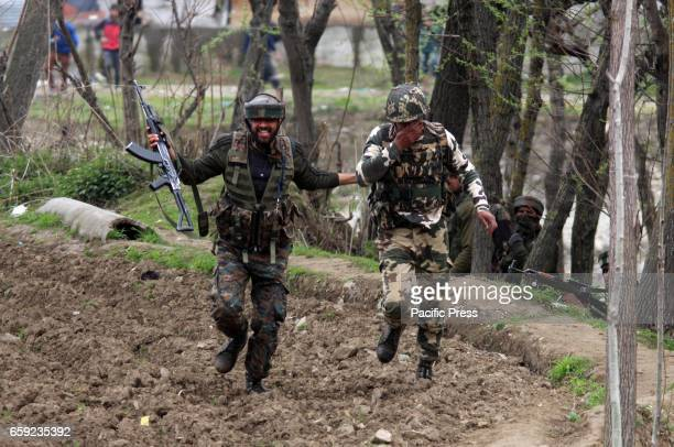Indian army soldier helping a wounded colleague near the gun battle site in Chadoora area of Central Kashmirs Budgam district One militant and three...