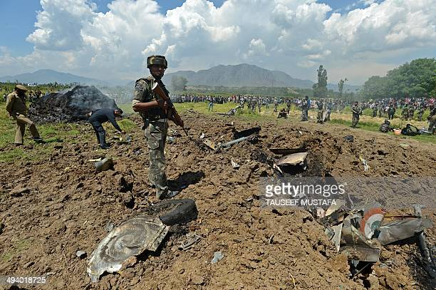 Indian army soldier stands near the wreckage of a MiG21 fighter aircraft of the Indian Air Force which crashed at Marhama Bijbehara village in...