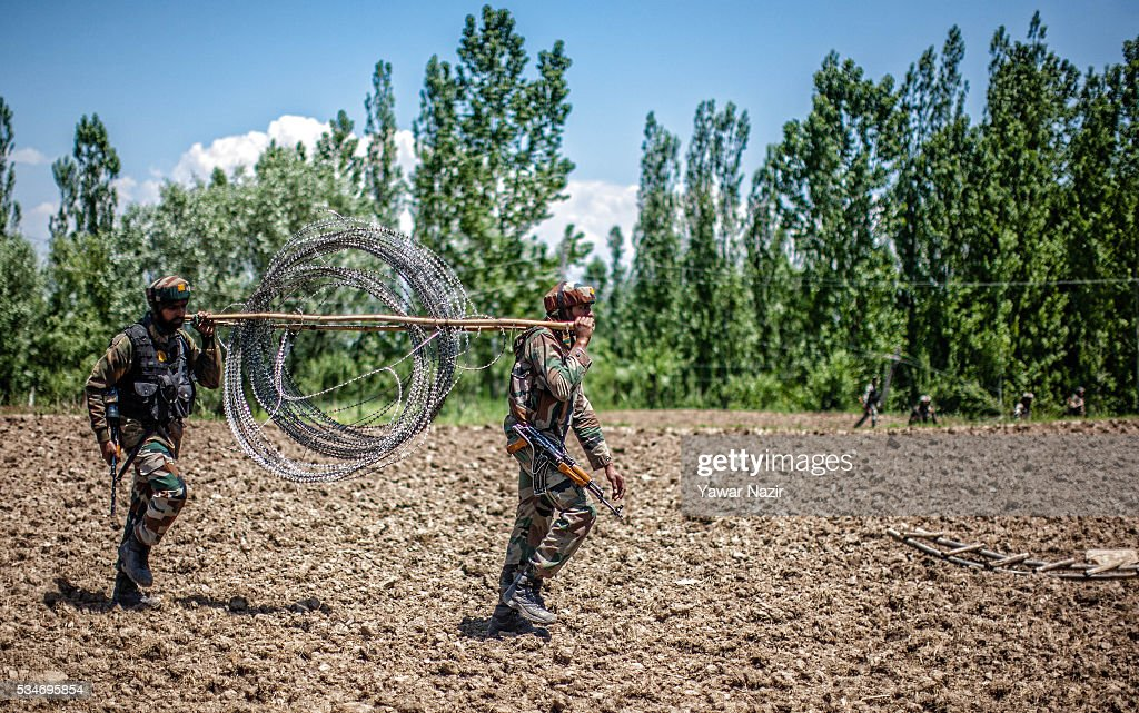 Indian army soldiers carry concertina razor wire at the site after a gun battle between militants and Indian government forces on May 27, 2016 in Khonchpur, 40 kilometers (25 miles) west of Srinagar, the summer capital of Indian administered Kashmir, India. Six rebels and an Indian army soldier were killed in two separate gun battles in the north Kashmir just four days after the Indian police claimed to have gunned down two unidentified militants in Sarai Bala area of Srinagar, a claim contested by the locals who say they were just students putting up in the locality.