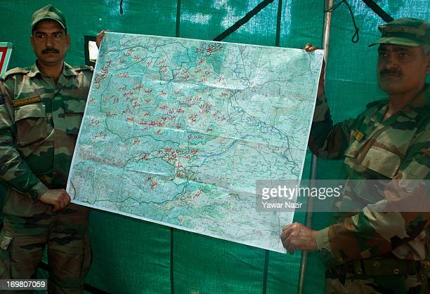 Indian army soldiers display a seized Pakistani topography map recovered from militants it says were killed on June 02 2013 in the border area of...