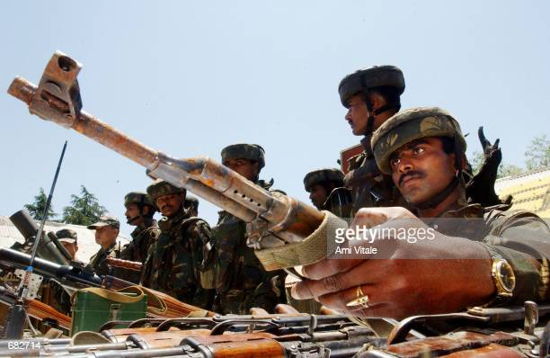 Indian Army soldiers display some arms allegedly recovered from militants who hid them in Lashteal forest June 8 2002 in Kupwara district 100...