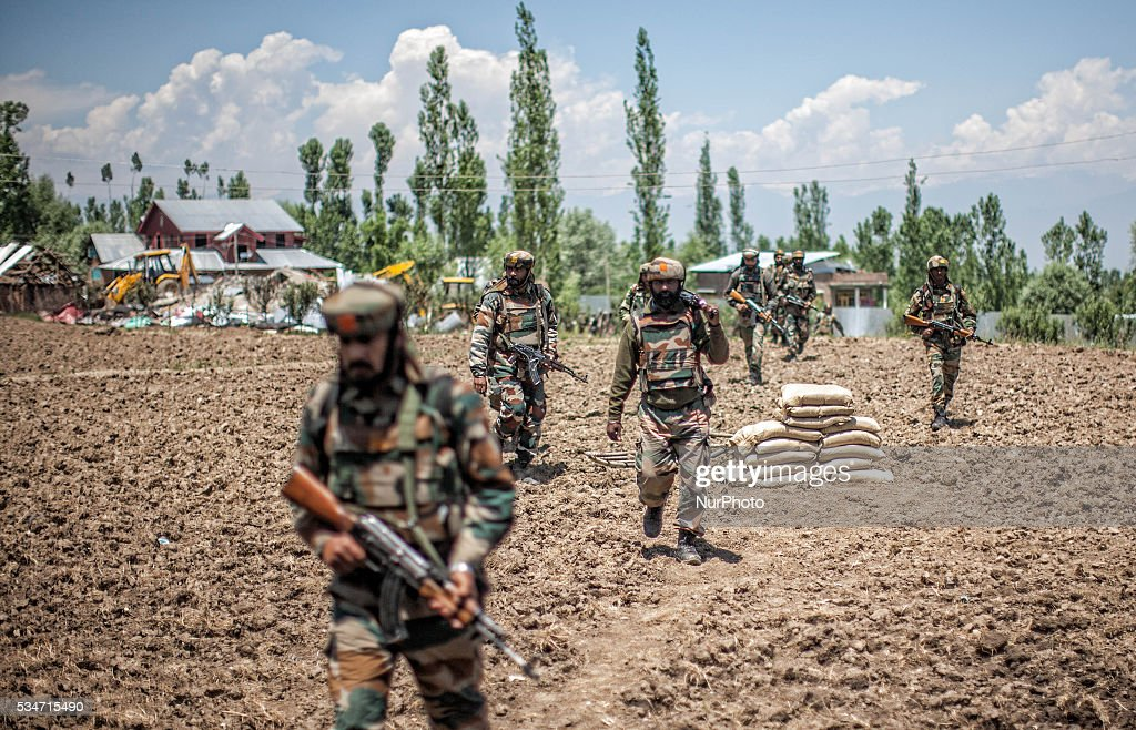 Indian army soldiers guard the area after the gun battle site where the militants were holed on May 27, 2016 in Khonchpur, 40 kilometers (25 miles) west of Srinagar, the summer capital of Indian administered Kashmir, India. Six rebels and an Indian army soldier were killed in two separate gun battles in the north Kashmir today.