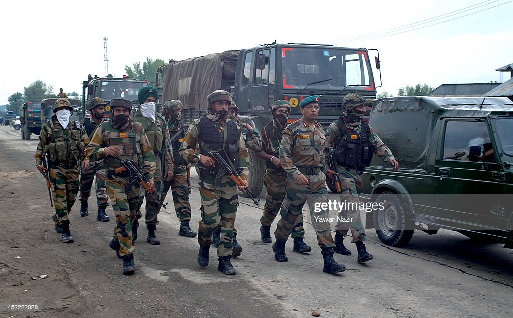 Indian army soldiers guard their convoy after a cab was hit by their vehicle killing at least six people July 16 2014 in Zaina Koot on the outskirts...