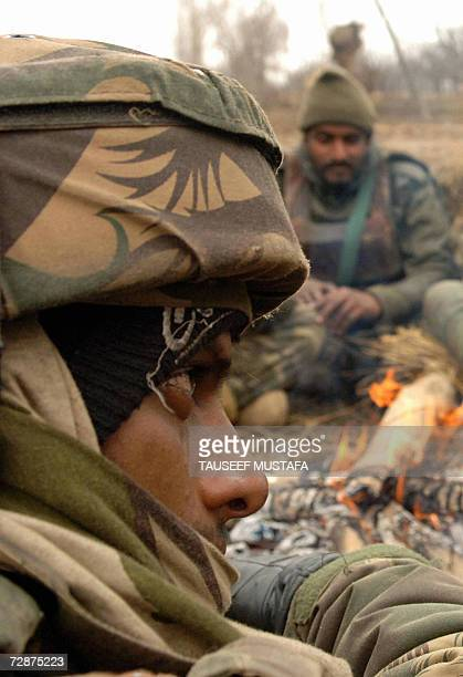 Indian Army soldiers keep themselves warm next to a fire during a gun battle with Muslim rebels in the Tilgam village of Pattan 40 kms north of...