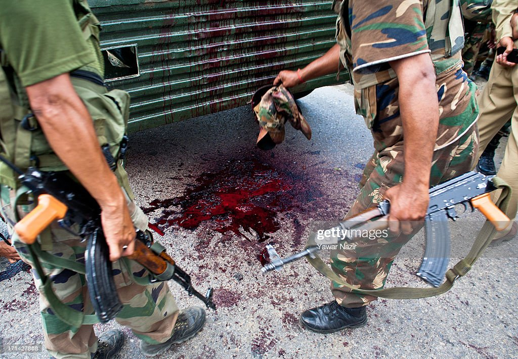 Indian army soldiers lift the caps of their comrades after a militant attack on their convoy on June 24, 2013 in Srinagar, the summer capital of Indian administered Kashmir, India. Suspected militants opened fire on an Indian army convoy on the outskirts of Srinagar, killing at least five and wounding seven others, ahead of Indian Prime Minister Manmohan Singh's visit to the disputed Himalayan region tomorrow. The militants fled from the scene and half an hour later hurled a grenade on Indian paramilitary forces in Barzulla area , some two kilometers away. Hizbul-Mujahideen, the largest guerrilla group fighting Indian rule since 1989, claimed responsibility for today's attack, and had just two days before gunned down two policemen in the heart of Srinagar city.