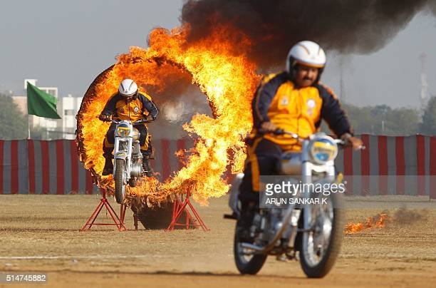Indian army soldiers members of the ASC Tornados motorcycle display team ride through a ring of fire during the combined display at Officer Training...