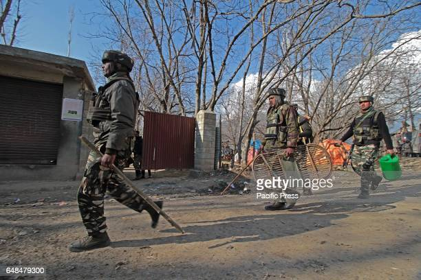 Indian army soldiers move towards the gun battle site in Hyuna village of Tral some 45 kilometers from Srinagar the summer capital of Indian...