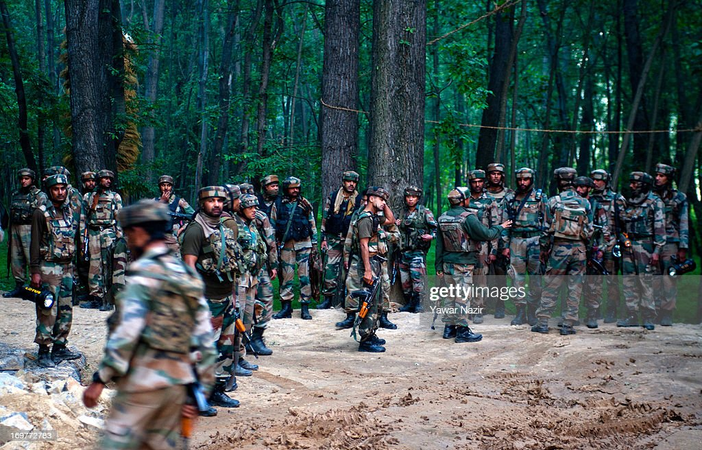 Indian army soldiers prepare to storm residential houses where militants took refuge on June 1, 2013 in Wachi, 49 km (30 miles) south of Srinagar, the summer capital of Indian administered Kashmir, India. Two militants belonging to Hizbul Mujahideen, the largest militant outfit operating in Indian Administered Kashmir, were killed in the gun battle that started between militants and Indian military forces in South Kashmir yesterday and ended this evening, police said here. This was the second gun battle between militants and Indian military forces in South Kashmir in the span of one week. Last week, militants killed five Indian army soldiers, while a militant was also killed.
