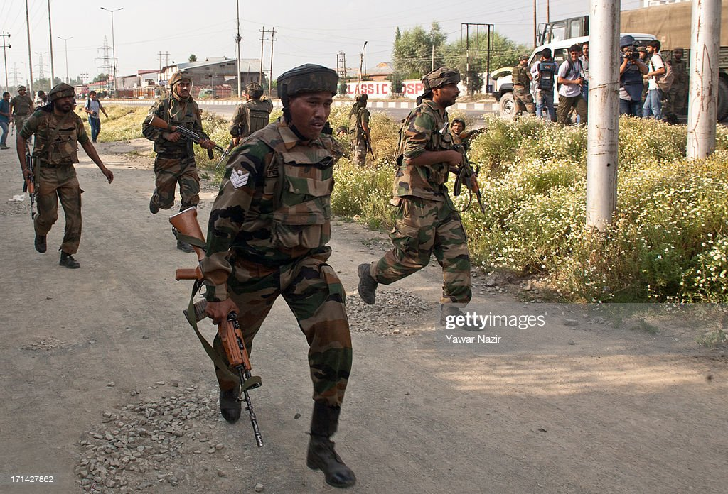 Indian army soldiers rush to the spot where militants attacked their convoy on June 24, 2013 in Srinagar, the summer capital of Indian administered Kashmir, India. Suspected militants opened fire on an Indian army convoy on the outskirts of Srinagar, killing at least five and wounding seven others, ahead of Indian Prime Minister Manmohan Singh's visit to the disputed Himalayan region tomorrow. The militants fled from the scene and half an hour later hurled a grenade on Indian paramilitary forces in Barzulla area , some two kilometers away. Hizbul-Mujahideen, the largest guerrilla group fighting Indian rule since 1989, claimed responsibility for today's attack, and had just two days before gunned down two policemen in the heart of Srinagar city.