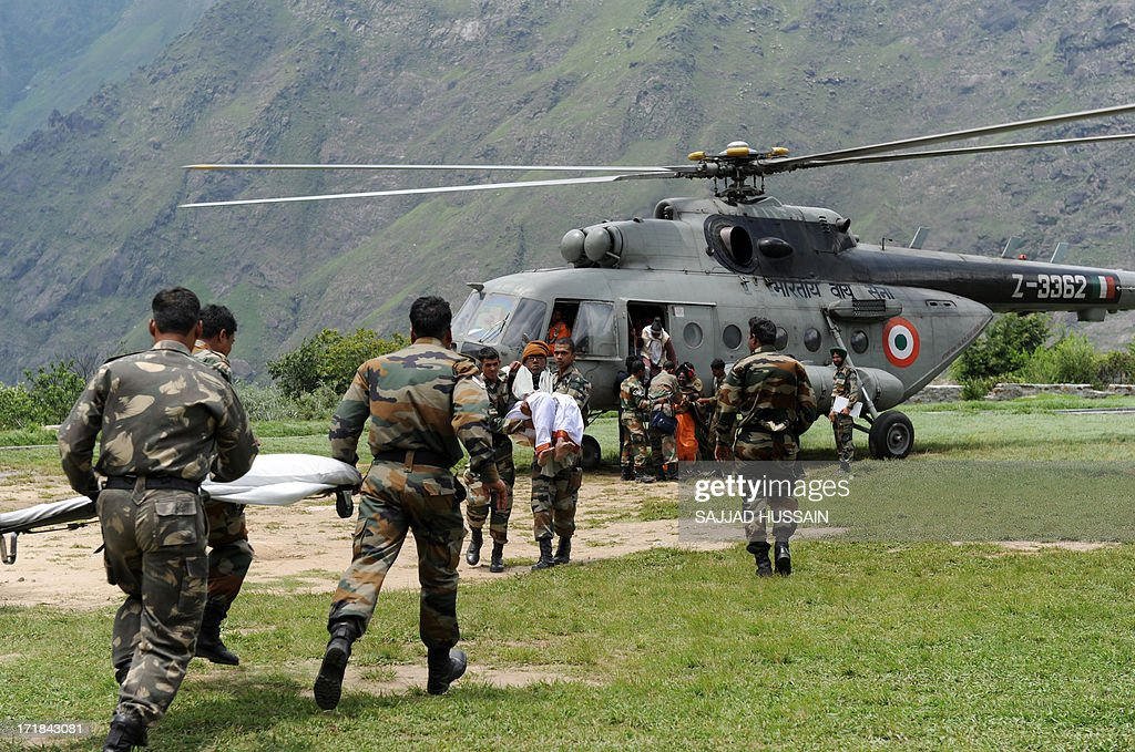 Indian army soldiers rush with a stretcher to carry an elderly Hindu Pilgrim from an Indian Air Force helicopter at Joshimath on June 29, 2013, after he was evacuated from the village of Badrinath in the flood effected northern Indian state of Uttarakhand. More than 100,000 mainly pilgrims and tourists have been evacuated from the disaster zone while some 4,000 remain in relief camps after the flash floods and landslides that hit the state on June 15.