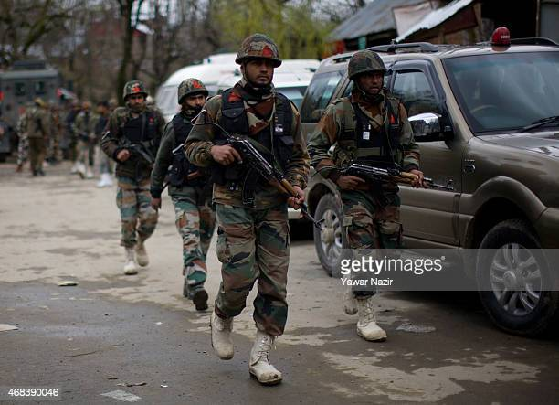 Indian army soldiers search the are where suspected militants killed an Indian policeman and an Indian army soldier during a gunbattle on April 02...