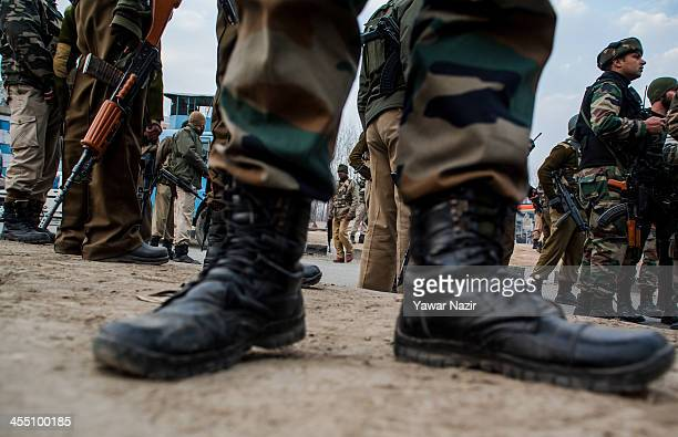 Indian Army soldiers stand guard at the site where suspected militants killed an Indian paramilitary officer and wounded another on the outskirts on...