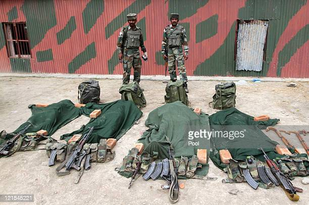 Indian Army soldiers stand guard in front the ammunition and bodies of suspected militants killed by the Indian Army on August 20 2011 in Gurez...