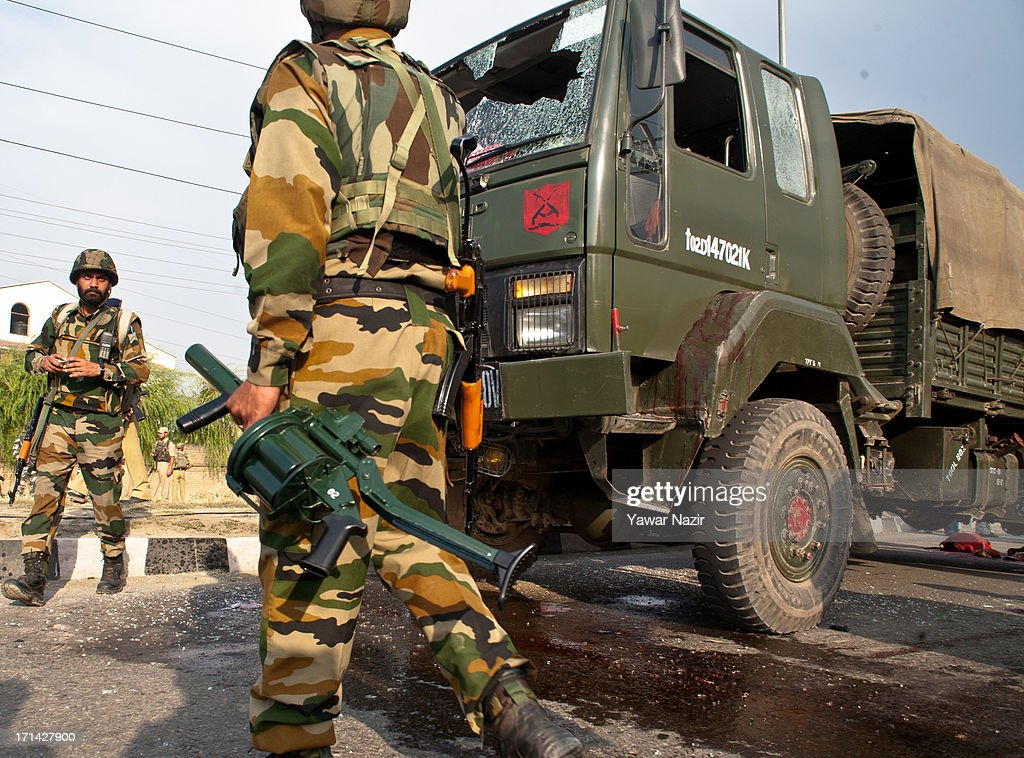 Indian army soldiers stand guard next to their vehicle which came under the attack of rebel militants on June 24, 2013 in Srinagar, the summer capital of Indian administered Kashmir, India. Suspected militants opened fire on an Indian army convoy on the outskirts of Srinagar, killing at least five and wounding seven others, ahead of Indian Prime Minister Manmohan Singh's visit to the disputed Himalayan region tomorrow. The militants fled from the scene and half an hour later hurled a grenade on Indian paramilitary forces in Barzulla area , some two kilometers away. Hizbul-Mujahideen, the largest guerrilla group fighting Indian rule since 1989, claimed responsibility for today's attack, and had just two days before gunned down two policemen in the heart of Srinagar city.