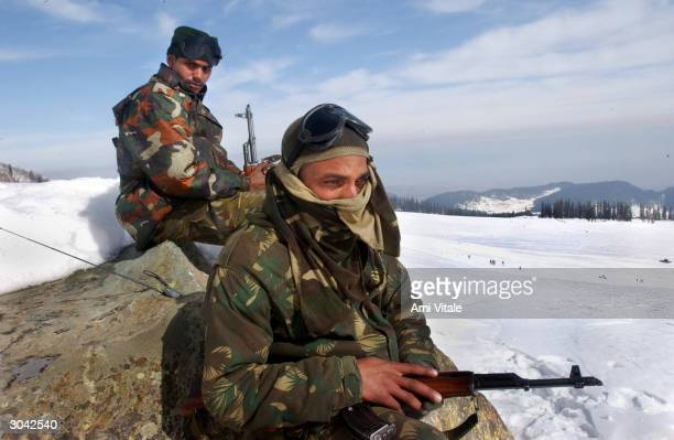 Indian army soldiers stand guard on the edges of the ski slopes during India's national winter ski championships March 4 2004 in Kongdoori Kashmir...