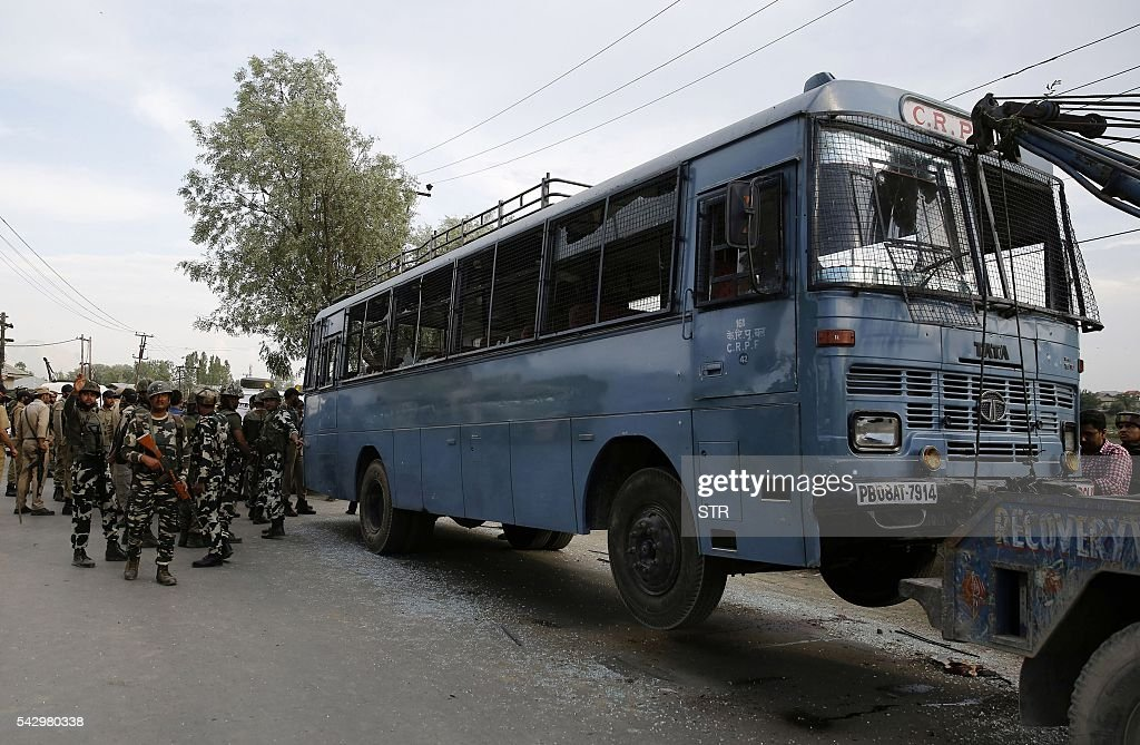 Indian army soldiers stand near a bus that had been carrying paramilitary troopers when it was attacked by suspected militants in Pampore, south of Srinagar, on June 25, 2016. At least eight Indian paramilitary soldiers and two suspected rebels were killed on June 25 near Srinagar in India-administered Kashmir when a group of armed militants ambushed the soldiers' convoy, police said. / AFP / STR