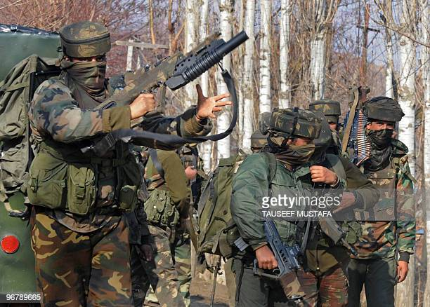 Indian Army soldiers stand near the scene of a gunbattle in Kuchwa Maqam village in Baramullah district north of Srinagar on February 172010 Two...