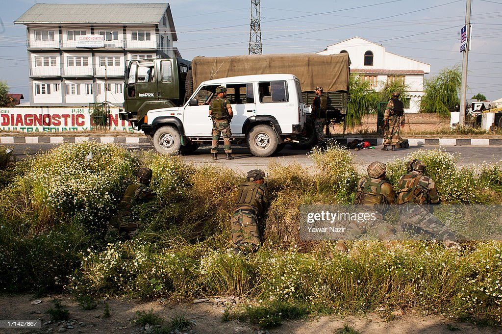 Indian army soldiers take positions after their convoy was attacked by militants on June 24, 2013 in Srinagar, the summer capital of Indian administered Kashmir, India. Suspected militants opened fire on an Indian army convoy on the outskirts of Srinagar, killing at least five and wounding seven others, ahead of Indian Prime Minister Manmohan Singh's visit to the disputed Himalayan region tomorrow. The militants fled from the scene and half an hour later hurled a grenade on Indian paramilitary forces in Barzulla area , some two kilometers away. Hizbul-Mujahideen, the largest guerrilla group fighting Indian rule since 1989, claimed responsibility for today's attack, and had just two days before gunned down two policemen in the heart of Srinagar city.