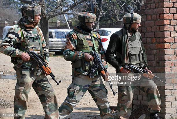 Indian army soldiers take positions against militants in an ongoing gunbattle on the outskirts of Srinagar on February 22 2016 Militant attackers...