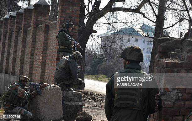 Indian army soldiers take positions against militants on the outskirts of Srinagar on February 21 2016 The death toll from a continuing gunbattle in...