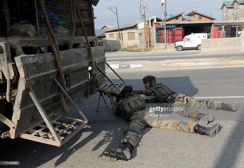 Indian army soldiers take positions at the scene of a deadly attack by armed rebels on the outskirts of Srinagar on June 24, 2013. Four soldiers were killed and six others were wounded in an attack on a convoy in Indian Kashmir on the eve of a visit by Prime Minister Manmohan Singh, the army said. AFP PHOTO/ Rouf BHAT