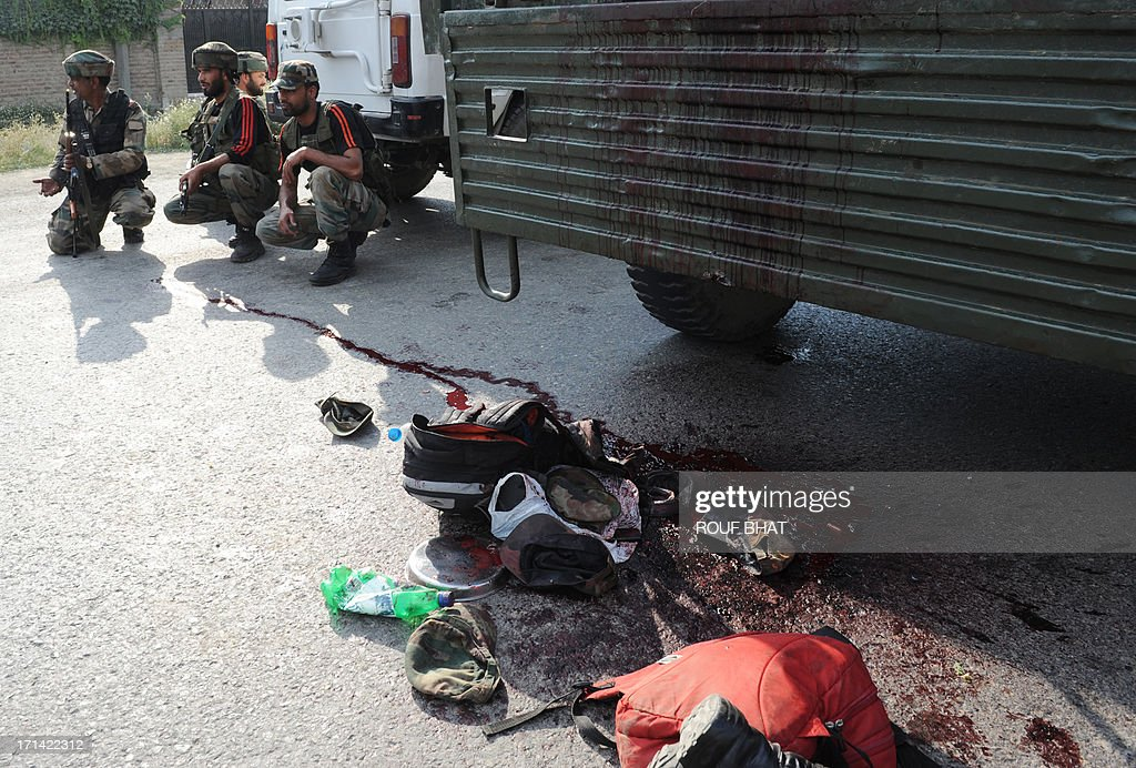 Indian army soldiers take positions near a damaged army vehicle at the scene of a deadly attack by armed rebels on the outskirts of Srinagar on June 24, 2013. Four soldiers were killed and six others were wounded in an attack on a convoy in Indian Kashmir on the eve of a visit by Prime Minister Manmohan Singh, the army said. AFP PHOTO/ Rouf BHAT