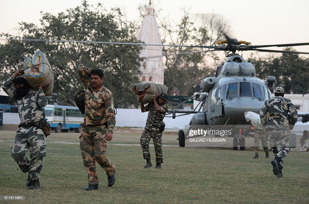 Indian Army soldiers unload supplies from an Indian Airforce helicopter at the Police Lines in Rohtak on February 21,2016 Ten people have died in caste protests which triggered widespread arson and looting in a north Indian state, police said February 21, as New Delhi faced a water crisis after mobs shut down a key supply. Thousands of troops with shoot-on-sight orders were deployed on February 20 in Haryana state, a day after week-long protests turned violent with rioters setting fire to homes and railway stations and blocking highways.