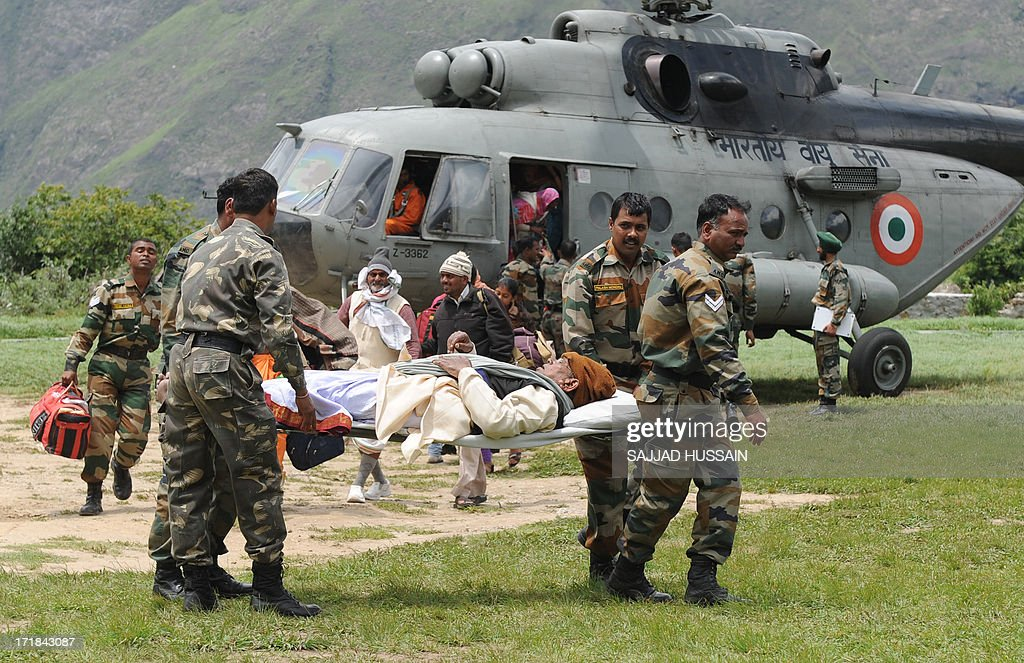 Indian army soldiers use a stretcher to carry an elderly Hindu Pilgrim from an Indian Air Force helicopter at Joshimath on June 29, 2013, after he was evacuated from the village of Badrinath in the flood effected northern Indian state of Uttarakhand. More than 100,000 mainly pilgrims and tourists have been evacuated from the disaster zone while some 4,000 remain in relief camps after the flash floods and landslides that hit the state on June 15.