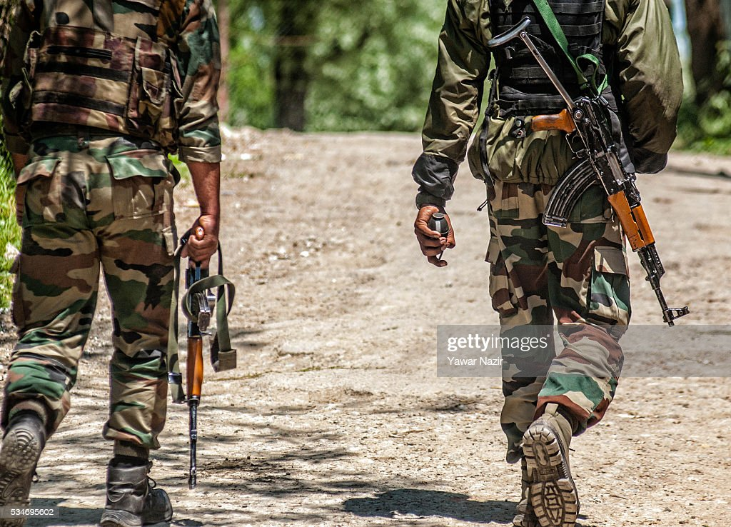 Indian army soldiers walk toward the gun battle site where the militants are holed up during a gun battle between militants and Indian government forces on May 27, 2016 in Khonchpur, 40 kilometers (25 miles) west of Srinagar, the summer capital of Indian administered Kashmir, India. Six rebels and an Indian army soldier were killed in two separate gun battles in the north Kashmir just four days after the Indian police claimed to have gunned down two unidentified militants in Sarai Bala area of Srinagar, a claim contested by the locals who say they were just students putting up in the locality.