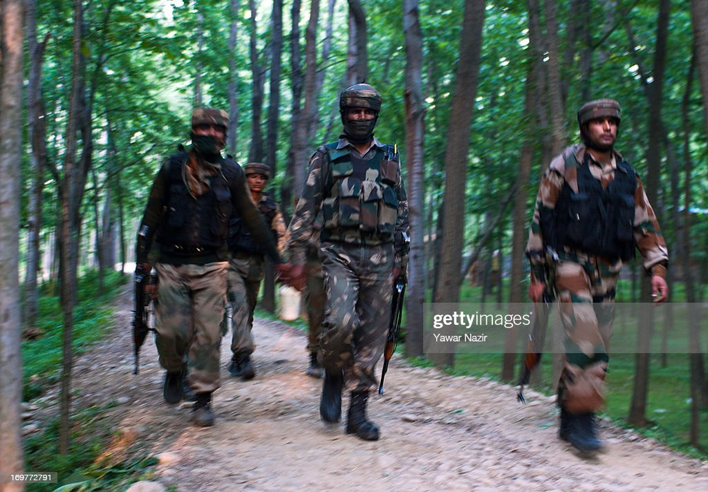 Indian army soldiers walk toward the site of a gun battle on June 1, 2013 in Wachi, 49 km (30 miles) south of Srinagar, the summer capital of Indian administered Kashmir, India. Two militants belonging to Hizbul Mujahideen, the largest militant outfit operating in Indian Administered Kashmir, were killed in the gun battle that started between militants and Indian military forces in South Kashmir yesterday and ended this evening, police said here. This was the second gun battle between militants and Indian military forces in South Kashmir in the span of one week. Last week, militants killed five Indian army soldiers, while a militant was also killed.