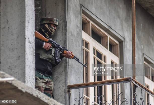 Indian army trooper aims his rifle towards a residential house where suspected rebels are fighting with Indian government forces during a gun battle...