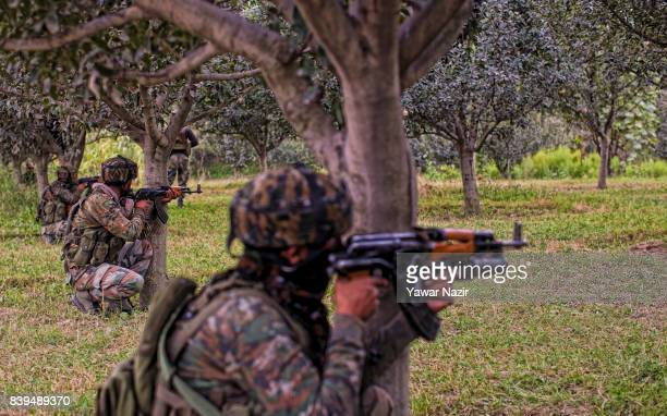 Indian army troopers aim their rifles in an apple orchard towards the camp where rebels are fighting with their comrades on August 26 2017 in Pulwama...