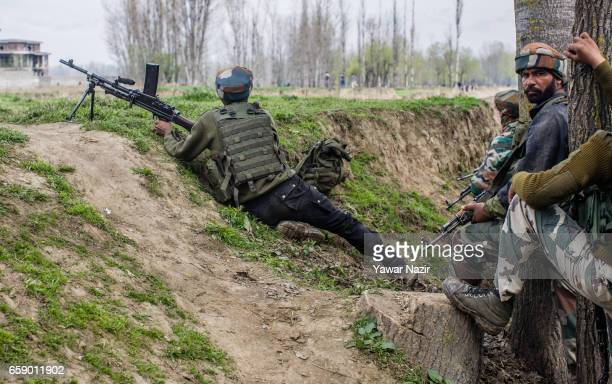 Indian army troopers aim their rifles towards a residential house where suspected rebels are trapped during a gun battle between Indian government...