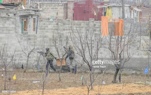 Indian army troopers carry an improvised explosive device before destroying the house where suspected rebels were trapped during a gun battle between...