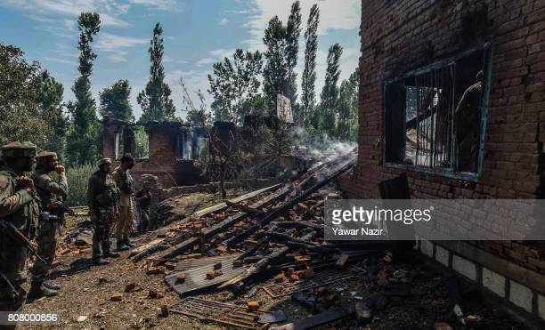 Indian army troopers inspect war ravaged houses where from rebels were fighting with them after a gun battle on July 4 2017 in Bahmnoo 60 km south of...